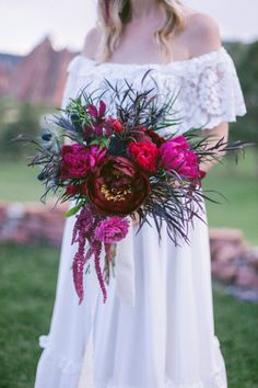 Bold boho bouquet with pops of the brightest pink: http://www.stylemepretty.com/colorado-weddings/littleton/2014/07/08/colorful-bohemian-wedding-inspiration/ | Photography: Sara Lynn - http://www.saralynnphoto.com/