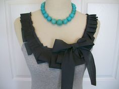 such a CUTE idea to doll up some tank tops! just use ribbon to create ruffles along the neckline, and adorn with a bow or flower! this picture isnt from a do it yourself but its obvious what they did hear!