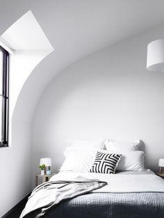 Black and white modern bedroom with cozy textiles and lots of natural light