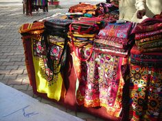 Sindhi embroidery work stall at Lok Virsa Mela, Islamabad, Pakistan. Lok means (folk), Virsa (heritage) and Mela (a bazar). It is a folk heritage event - an annual spring event in which craftsmen and craftswomen from all four provinces of Pakistan exhibit their artwork (handicrafts, embroidery, regional food stall) in one compound. The products are for display/sale.    Photograph: hand-embroidered handbags/shirts/wallets.  Photography: Zehra Naqavi (Architect/artist).    April 11, 2012