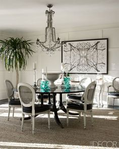 In the dining room of Cynthia Frank's Southampton home the dining table came from a Sotheby's auction, the antique chairs were purchased at Doyle New York, and the chandelier is a Paris flea-market find; the photograph is by Nathaniel Kramer, and the rug is by Stark.