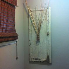 Old cabinet door (junk shop) w glass vase (pottery barn) in my bathroom