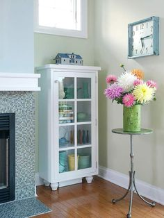 I adore this glass-front cabinet (and the little stand with fresh flowers.)