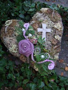 Herz mit verschiedenen Moosen liebevoll verarbeitet. Mit frischem Grün, das mit der Zeit eintrocknet, Filzkordel und Perlen. Hingucker ist eine wunderschöne lila Filzrose. Mit dem Kreuz auch sehr...