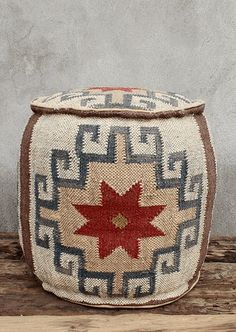 Woven jute, cotton-filled pouf decorated with a kilim dhurrie pattern. Indigo and Cranberry pattern on natural field.
