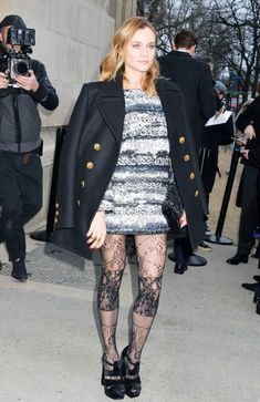 Diane Kruger is head-to-toe Chanel in a black coat, printed dress, lace tights and bag