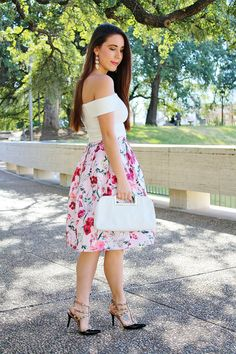 Pink floral A-line skirt; white off-the-shoulder top; white Michael Kors Berkley clutch; black rockstud pumps; Spring style, spring outfit