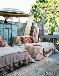 "Christina Karras' 1920s Spanish-style bungalow// Two outdoor chaises are draped for lounging under a vintage striped beach umbrella. Surfboards stand at the ready, something Karras acknowledges as ""super California."""