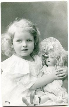 Vintage photo of a pretty little girl with her doll.