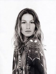 Gisele Bündchen with minimal, natural makeup, loose, long waves and a center part.