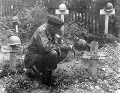 An American soldier stands over the grave of John Simcox, one of the POWs who died in the Berga concentration camp. A special area of the Berga cemetery was set aside for the bodies of 22 Americans, some of whom were buried in the same grave without coffins. The helmet displays the insignia of the 28th Division. (NARA Photo).