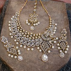 Wedding Bridal Necklace set with matching dangle earrings and tikka studded with Simulated White Cz Kundan and Faux Pearl Beads    Gold Tone, handcrafted with high quality cz and kundan .    Earrings - Measures (approx) (L)90mm x 30mm(W) OR 3 1/2\
