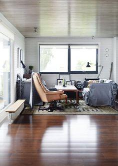 SPENNENDE KONTRASTER: I denne stuen er avslappede sofaer i lin blandet med en retrostol i skinn, en arkitektlampe og et tradisjonelt teppe. På toppen av den ene gulvmonterte radiatoren er det montert en treplanke, slik fungerer den også som benk foran vinduet.