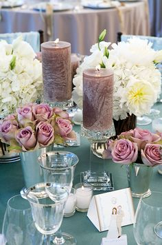 Hydrangea and roses placed in silver metallic vases are paired with candles in varying heights.