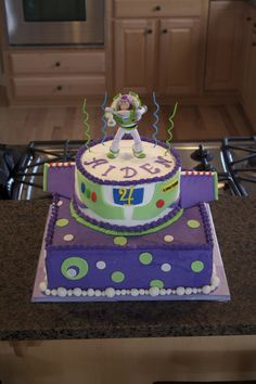Buzz Lightyear Chocolate and vanilla cake tiers, iced in buttercream, fondant accents (including Buzz wings), toy Buzz on top of cake.