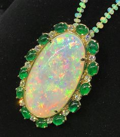 @gem.addict. Gorgeous 58ct white opal surrounded  by a halo of cabochon Emeralds & brilliant cut diamonds. Opals play of color is caused by spheres of silica that are reflecting light back out of the stone. #opal #opalnecklace #diamonds #brilliantcut #emerald #cabochon #18karat #gold #pendant #playofcolors #halo #bead #oval #silica #poc #ethiopian