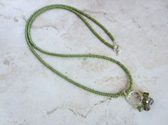 A modern and trendy long green necklace!  Love the smoky brown and green crystal pendant!