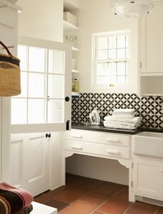 This dog nook is tucked away in the world's cutest laundry room and is framed wi. This dog nook is tucked away in the world's cutest laundry room and is framed with decorative braces. Built In Dog Bed, Black And White Backsplash, White Tiles, Black Counters, Red Tiles, Marble Countertops, Dog Nook, Spanish Modern, Spanish Colonial