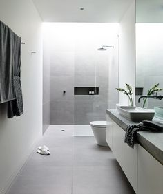 Melbourne is the location of the Canny-designed Lubelso Hawthorn Concept Home where one of the bathrooms has large, soft grey tiles on the floor that continue up the sides of the shower walls. A skylight above the shower keeps the space full of light.  Photo by Derek Swalwell