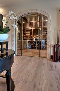 Wine cellar has glass doors as window into the vino bottle collection. Like how it adjoins the bar room with pool table and hardwood floors. Billiards & bubbly anyone?