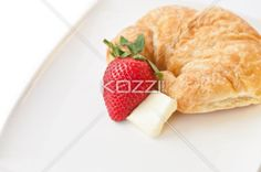 image of croissant with strawberry and cheese. - Close-up shot of croissant with strawberry and cheese against white background.