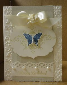 I would do this with seam binding instead of the satin ribbon, it gives it that softer more antique look. I would also probably use Tea Dye ink on the embossed background, just to make it blend in a little better.