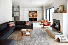 """The family room is dominated by a utilitarian Ikea sectional. """"We don't want to be worried about our couch,"""" Mr. Faherty said. """"This is where we hang out. And where the kids sometimes give singing and acting performances."""" The orange chairs were flea-market finds."""