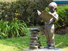 """The bronze sculpture of a young boy reading """"Book Worm"""" located outside the Doylestown Public Library. Doylestown, Pennsylvania.  Sculpture designed by Gary Lee Price."""