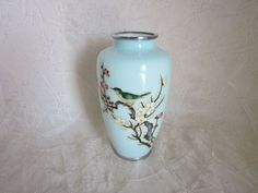 This vase has a very unique color, sort of a pastel teal. The design is well done, and the vase is in quite good condition. There is no damage to the design or exterior.