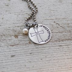"A sterling silver disc, just under 1"" in diameter, is hand stamped with the word ""unconditional"" along with our exclusive cross. It hangs from an 18"" stainless steel chain (which is very silver colored in person, not black as the photo shows), paired with a freshwater pearl.Items ship within 2 weeks and come boxed, ready for gift giving.This necklace is a copyrighted TheRustedChain original ©."
