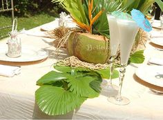 Beach themed rehearsal dinner - centerpiece using coconuts and tropical foliage