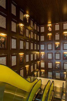 Le marron boisé des murs et le classicisme ironique de ces portraits d'animaux affichés comme dans la galerie d'un musée désuet sont le parfait écrin pour le modernisme de l'escalator en métal et jaune néon. Le tout signé Philippe Starck.
