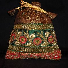 Brown and green potli bag designed with resham, zari, cutbeads and sequins dori work.