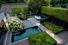 / This backyard features a natural pool, shaped greenery, a dining space, and an area perfect for sunbathing.
