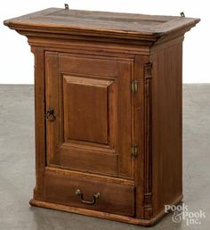 Pennsylvania poplar hanging corner cupboard, 19th c., with a single raised panel door over a full width drawer, flanked by reeded quarter columns, 26'' h., 17 1