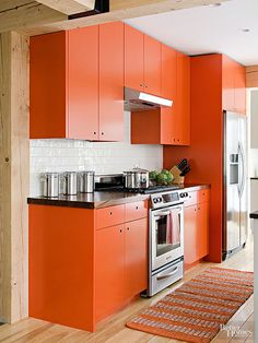 Give your kitchen a fresh start with a juicy citrus hue. Bold orange cabinet color provides a brilliant contrast to this room's crisp black countertops and shiny white backsplash. All values of gray -- muted to charcoal -- work well with a range of oranges. Paint Color:Sherwin-Williams, Raucous Orange, SW-6883.