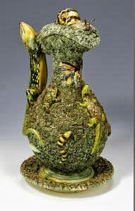 A Portuguese Palissy-style ewer, basin and stand, circa 1870 -  Modelled by José Alves Cunha, the thick green moss-ground applied with various reptiles and insects, the handle shaped as a lizard, the finial on the cover with a naturalistically modelled snail, 38.5cm high impressed factory mark to the base of the plate
