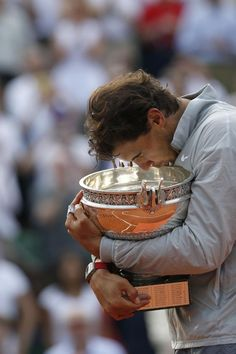 Spain's Rafael Nadal kisses the trophy after winning the final of the French Open tennis tournament against Serbia's Novak Djokovic at the Roland Garros stadium, in Paris, France, Sunday, June 8, 2014. Nadal won in four sets 3-6, 7-5, 6-2, 6-4. (AP Photo/Darko Vojinovic)