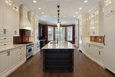Massive galley style kitchen with white cabinets flanking the dark wood and white top island running down the center of the kitchen space.