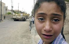 A young Iraqi girl cries as a British Challenger tank moves in on the Baath party office in Basra April 8, 2003. (Odd Andersen/AFP/Getty Images) #