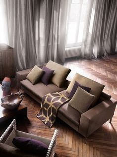 Lizzo -  Bauhaus Fabric Collection - Brown suede effect sofa, purple and sand coloured cushions, brown and gold fabric, thin grey curtains, wood table and bowl, brown armchair