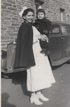A smiling nurse wearing a wonderful, classic wool cape, holders a youngster outside on the street in this charming image