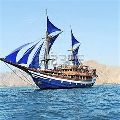 Vintage Wooden Ship with Blue Sails near Komodo Island, Indonesia.