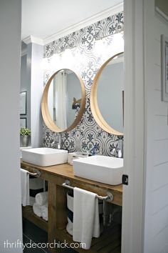 bathroom reno with tile wall and round mirrors