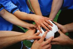 This soccer team is all putting their hands together as one before the game to get pumped up.