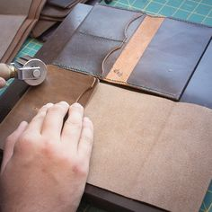 To make sure the pockets line up correctly,  I use one of our first passport cases as a guide. I'm flattening the edges with a roller before gluing and stitching.