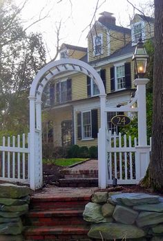 love the white picket fence with arch house is amazing