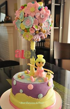 , I made this Lalaloopsy Easter Cake. The topiary was made from a styrofoam ball covered in cling wrap then painted with candy melt.I also used candy melt as glue for all the fondant flowers and candies.   For Lalaloopsys dress, I discovered a new art. I used gelatin sheets to achieve the sheer look. Tutorial on which I found here http://confessionsofascratchbaker.blogspot.ca/2011/05/my-first-tutorialgelatin-sequins.html  www.fb.com/sweetsbydonna