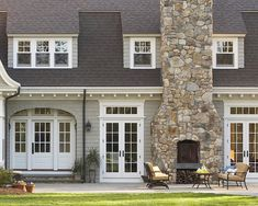 Outdoor stone fireplace and chimney on a traditional gray shingled house with white trim....love the french doors with transoms