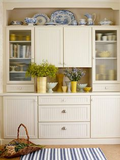 """Mudroom - Eye-Catcher: Opposite the back door, the hutchlike cabinetry grouping creates the second zone. The """"hutch"""" serves double duty as the room's focal point and as a drop spot for mail. There are display areas for the homeowners' dish collection. Bags and daily mail can rest on the open spot, and drawers hold everything from party supplies to lightbulbs."""